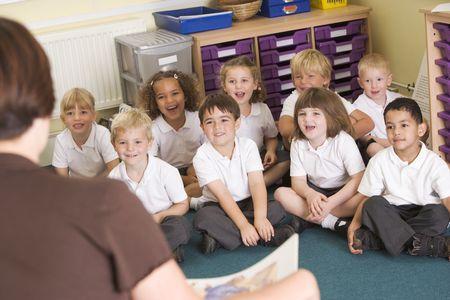 Los estudiantes en la clase sentados en el piso con el profesor en primer plano (atención selectiva)