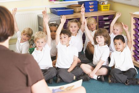 Students in class sitting on floor volunteering for teacher (selective focus) photo