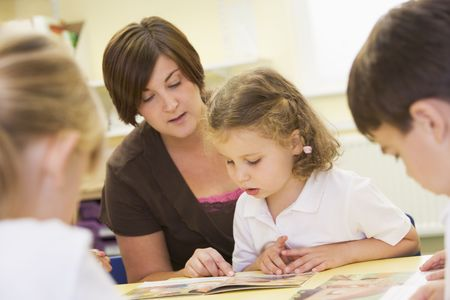 educadores: Estudiante en clase con el profesor de lectura (enfoque selectivo)  Foto de archivo