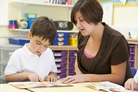 Student in class with teacher reading Stock Photo - 3223722