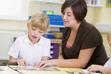 school age boy: Student in class with teacher reading Stock Photo