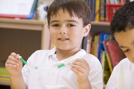 facing on the camera: Student in math class with counting beads Stock Photo