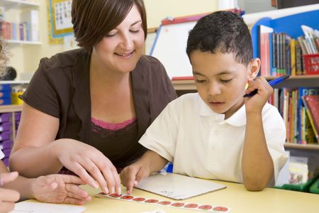 literacy instruction: Student in class with teacher learning numbers Stock Photo