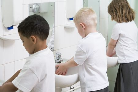 personal hygiene: Students in bathroom at sinks washing hands Stock Photo