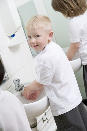 Students in bathroom at sinks washing hands photo