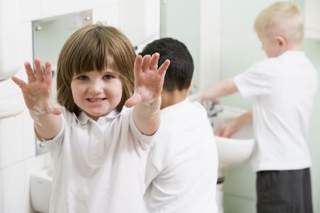 educating: Students in bathroom at sinks washing hands with one holding up soapy hands (selective focus) Stock Photo
