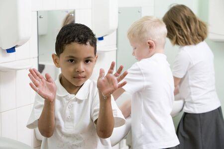 manos limpias: Los estudiantes de cuarto de ba�o en los sumideros de lavar las manos con un jab�n hasta la celebraci�n de las manos (atenci�n selectiva)