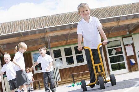 Los estudiantes de juego al aire libre durante un receso de tres ruedas con una scooter (atención selectiva)