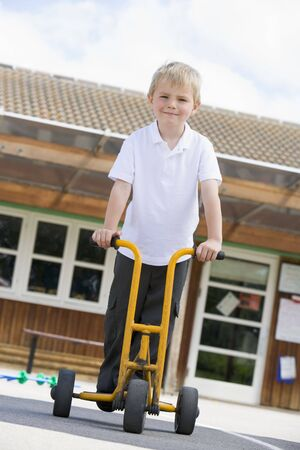 Student outside school on tricycle scooter photo
