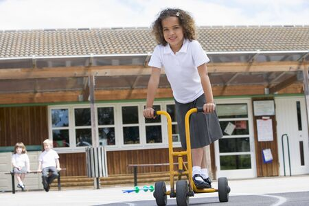 school playground: Student outside school on tricycle scooter Stock Photo