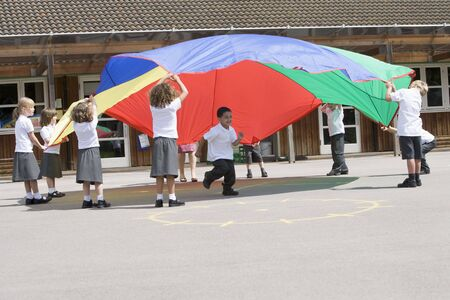 schoolyard: Students outdoors during recess playing with a parachute