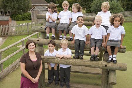 uniform school: Los estudiantes sentados al aire libre en estructura de madera con el profesor de pie junto a ellos