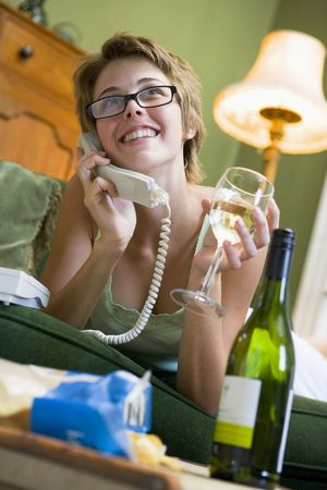 Young woman at home talking on telephone photo