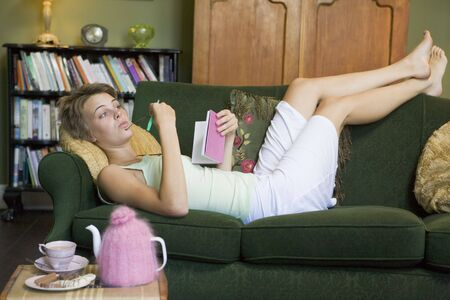 Young woman lying on sofa at home writing in her diary photo