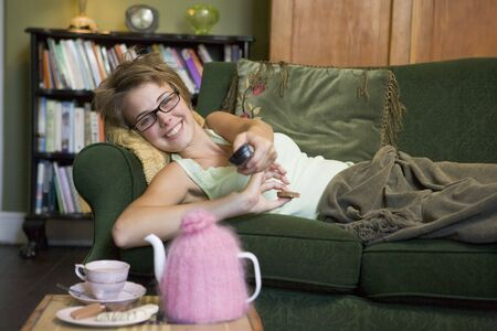 Young woman lying on sofa at home watching television Stock Photo