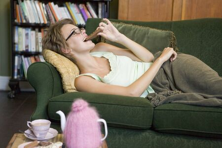 indulging: Young woman lying on sofa at home eating chocolate