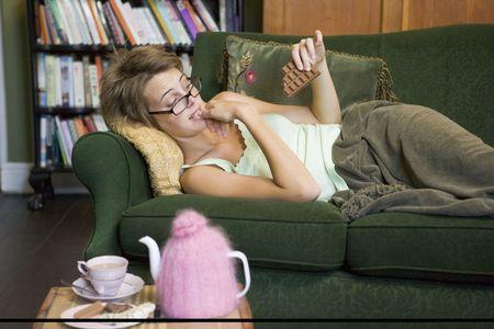 guilty pleasure: Joven mujer se extiende en sof� en casa comiendo chocolate  Foto de archivo