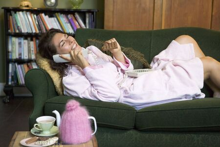 Young woman lying on sofa at home eating chocolate and talking on telephone photo