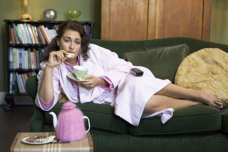 Young woman lying on sofa at home eating cookies and drinking tea Stock Photo - 3218077