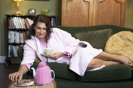 Young woman lying on sofa at home eating cookies and drinking tea