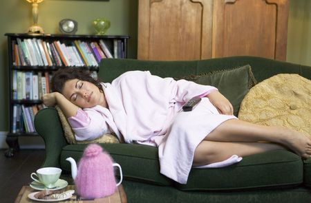 Young woman lying on sofa falling asleep while watching television Stock Photo