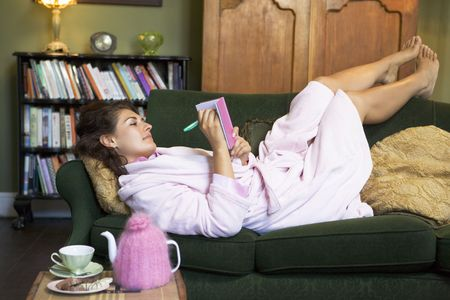 girls feet: Young woman lying on sofa at home writing in her diary
