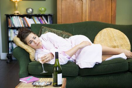 Young woman lying on sofa smoking and drinking wine photo