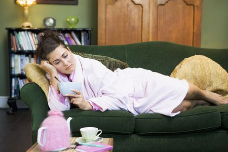 tea breaks: Young woman lying on sofa at home eating a sweet treat Stock Photo