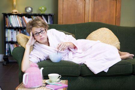 guilty pleasure: Joven mujer se extiende en sof� en casa comiendo un dulce tratar