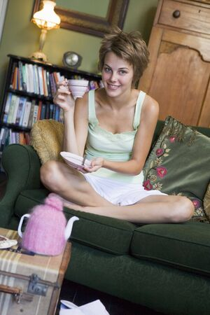 tea breaks: Young woman sitting on sofa at home drinking tea