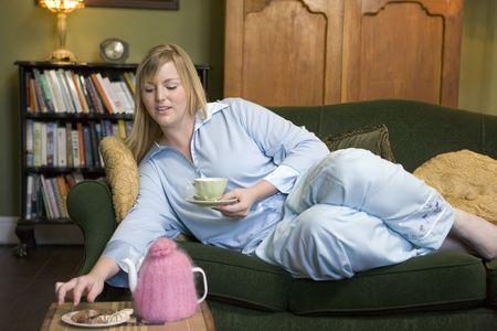 tea cosy: Young woman lying on sofa at home eating cookies and drinking tea