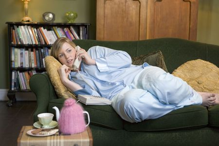 Young woman lying on sofa at home talking on telephone photo