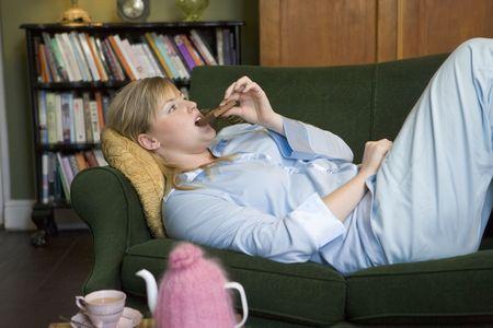 donne obese: Donna giovane disteso sul divano a casa di mangiare cioccolato