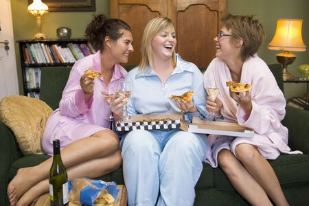 Three woman in night clothes sitting at home eating pizza photo