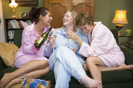 Three woman in night clothes sitting at home drinking wine Stock Photo - 3226335