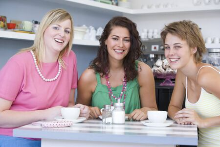 friends having tea series: Tres j�venes mujer sentada en una mesa y bebiendo t�