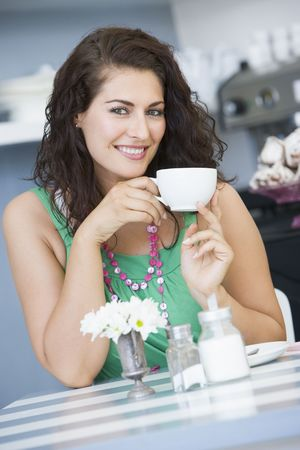 tilted view: Young woman sitting at a table drinking tea