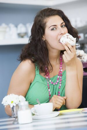 tea breaks: Young woman sitting at a table eating a sweet treat Stock Photo