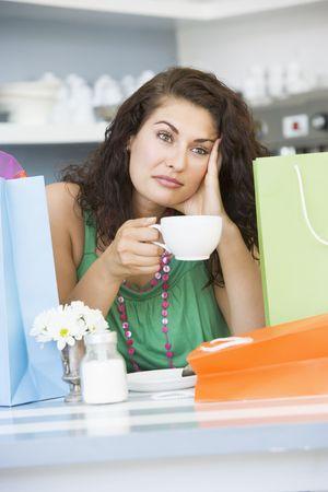 ambivalence: Jeune femme assise � une table en prenant une pause des centres commerciaux et boire du th�  Banque d'images