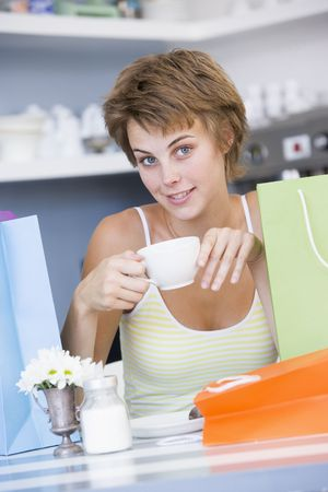friends having tea series: Young woman sitting at a table taking a break from shopping and drinking tea