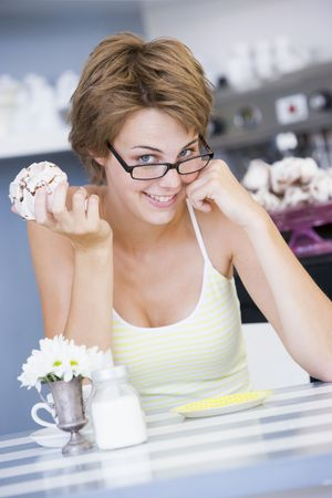 Young woman sitting at a table eating a sweet treat photo