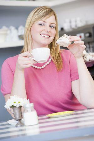 guilty pleasure: Joven mujer sentada en una mesa de beber t� y comer un dulce tratar