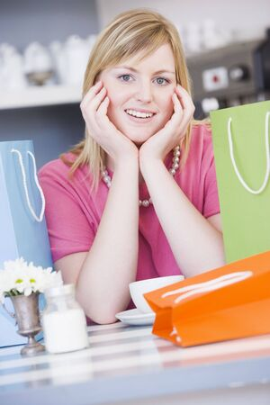 Young woman sitting at a table taking a break from shopping Stock Photo - 3202833