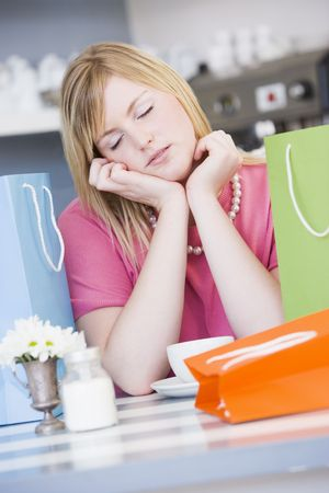 ambivalence: Exhausted young woman sitting at a table taking a break from shopping Stock Photo