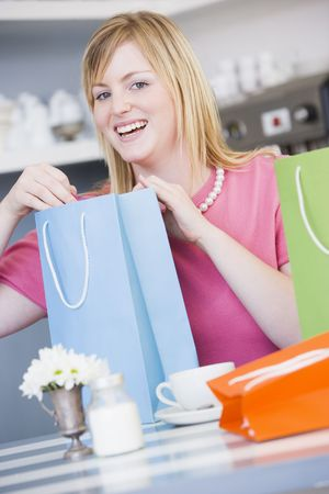 Young woman sitting at a table taking a break from shopping Stock Photo - 3223716