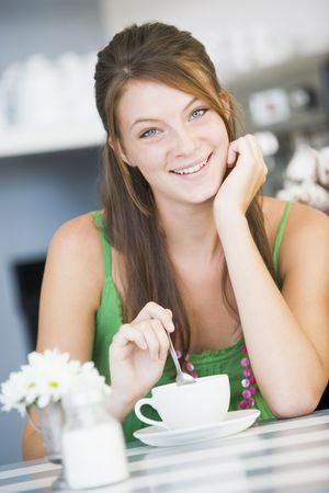 coffee breaks: Young woman sitting at a table drinking tea