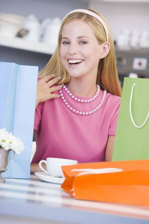 friends having tea series: Young woman sitting at a table taking a break from shopping Stock Photo