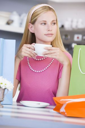 Young woman sitting at a table taking a break from shopping and drinking tea Stock Photo - 3226361
