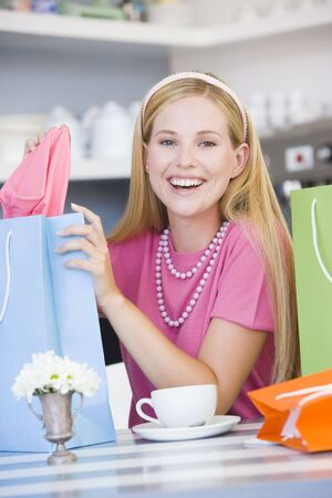 Young woman sitting at a table taking a break from shopping Stock Photo - 3225486