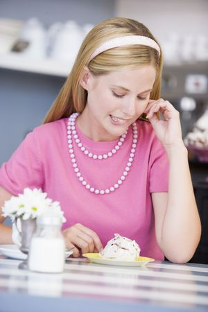 friends having tea series: Young woman sitting at a table eating a sweet treat Stock Photo